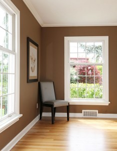 White windows on brown walls with chair in corner